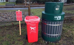 red bin for dog poop and green garbage bin