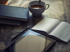 A tablet with a couple of notebooks and a cup of coffee on a wooden table