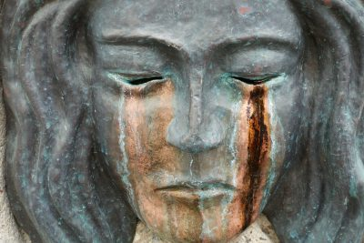 close up image of a crying stone angel