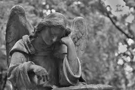 grey tone image of a stone angel in a sad pose