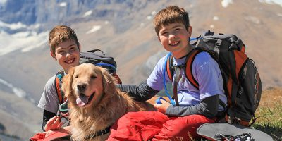 Two boys wearing backpacks sitting with a Golden Retriever